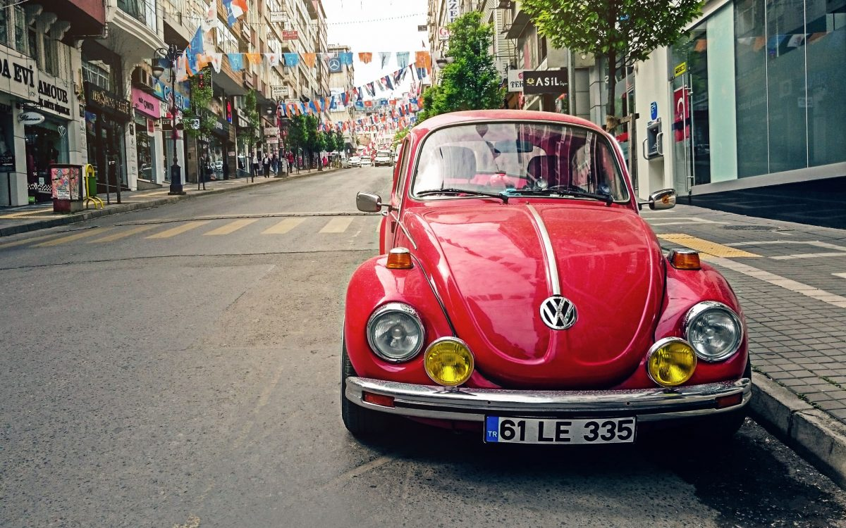 red-volkswagen-beetle-parked-at-road-side-near-pedestrian-131811